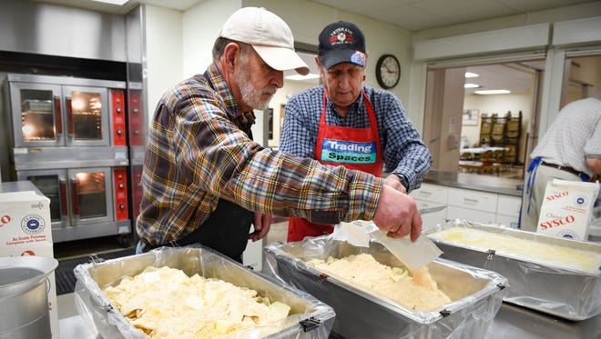 Michael Kowski, left, and Bill Eiffert prepare pans of au gratin potatoes in preparation for a fish fry Friday, March 11, at the Church of St. Anthony.