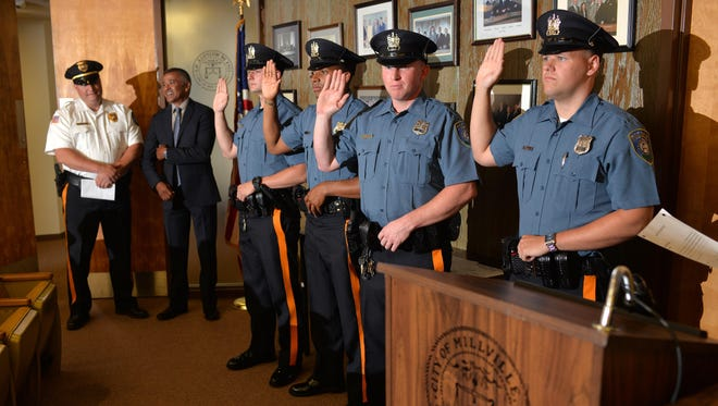 Four new Millville police officers, Bradley Moore, Albert Chard Jr., Anthony Jones, and Jonathan Harris (pictured from right to left) are sworn in at Tuesday night's City Commission meeting. Far left: Chief Jody Farabella and Mayor Michael Santiago watch.