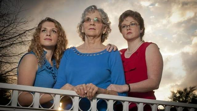 DeAnna Corbin, center, is with her daughters Abigail Corbin, left and Jennifer (Jenny) Corbin, 31, outside of their Jacksonville, Florida home.  DeAnna's ex-husband and the two sisters' father, Robert Lee Corbin, was among two men killed in an industrial accident in Louisville in 2009.