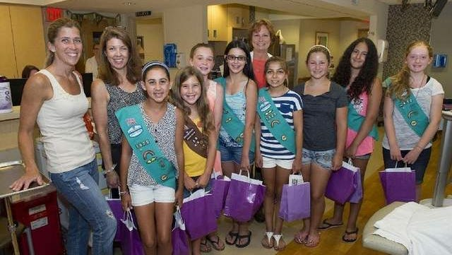 Girl Scouts Troop #1620 delivers purple goodie bags to cancer patients at Monmouth Medical Centers Outpatient Infusion Centers.