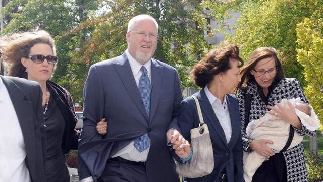 A smiling Harvey Whittemore and family members enter federal court in Reno Monday Sept. 30, 2013 for sentencing.