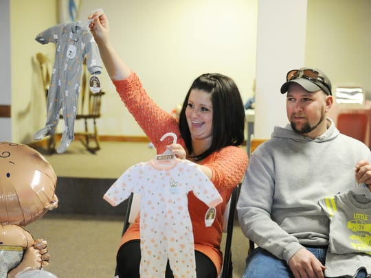 ERIN McCRACKEN / COURIER & PRESSSara McCarter shows off  outfits to her family as she and her husband, Zach, open presents for their twins, Blaine and Mila on at St.Vincent Catholic Church in Vincennes, Ind., on Feb. 7, 2015.