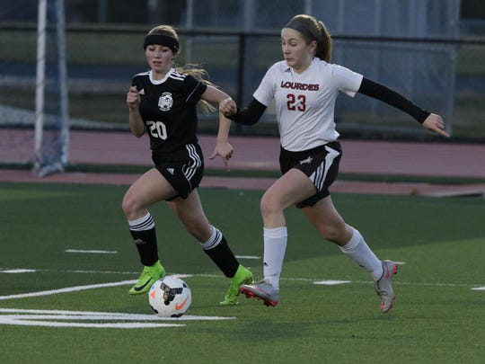 Lourdes Academy's Maggie Berenz keeps the ball away from Hustisford/Dodgeland United's Alexis Becker duringTuesday's game.