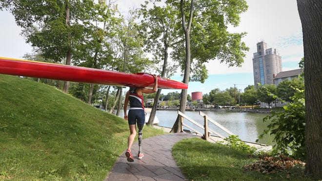 Anja Pierce, who hopes to compete in canoeing in next year's Paralympics, hauls her specially made kayak down to the public docks and the Erie Canal for a morning training session in Pittsford earlier this month. She lost her leg to bone cancer as a child.