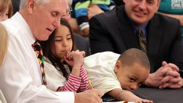 Gov. Mike Pence signs a bill creating a preschool voucher program as 5-year-old Rosie Chavez and 4-year-old Tre Embry help with the pens that were later given to lawmakers who helped pass the bill.