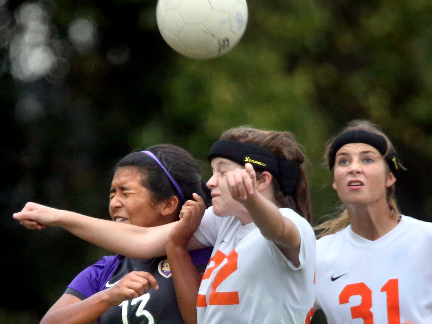 Smyrna's Brenda Cernas (13) and Blackman's Emily Nash (22) both try to head the ball as Blackman's Amelia Goodnight (31) watches from behind during the first half Monday at Blackman.