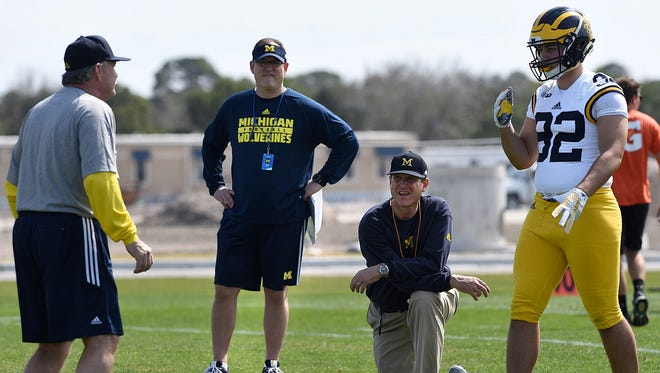 Michigan's head coach Jim Harbaugh (kneeling) watches defensive lineman Cheyenn Allen during a workout held in Bradenton, Fla. Though not a satellite camp in the truest sense of the word, such drills held in s location more than 1000 miles from the school's Ann Arbor campus may be in jeopardy.