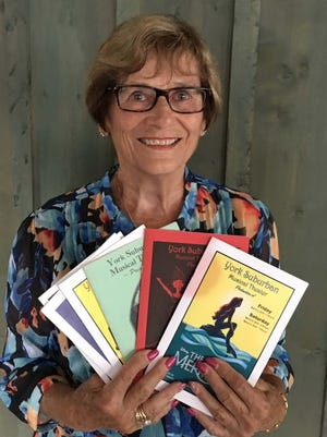 Myrna Schaszberger holds just a few of the programs from her long career as a musical theater director at York Suburban High School.