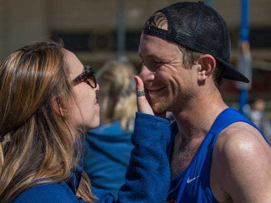 Rob Lugg, the men's marathon winner, gets a hug from girlfriend Jaquelyn Davis after finishing the Downtown River Run on Sunday.