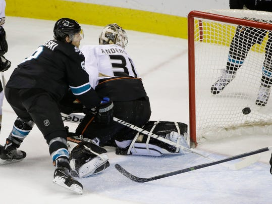Anaheim Ducks goalie Frederik Andersen, right, of Denmark, is beaten for a goal on a shot by San Jose Sharks' Patrick Marleau as center Joe Pavelski, left, watches during the first period of an NHL hockey game on Thursday, March 20, 2014, in San Jose, Calif. (AP Photo/Marcio Jose Sanchez)