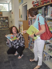 Children's librarian Lisa Burtz helps Gayle Nelson find a book about a hippopotamus for her granddaughter. Bonita's public library reopened Tuesday, Dec. 27, after being closed for about three months so that Hurricane Irma damage could be repaired.