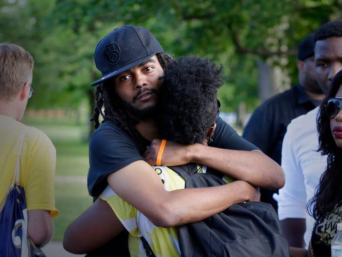 Frank Nitty, a community activist, hugs Markasa Tucker