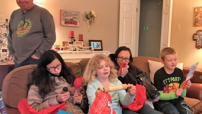 Patrick Ramsey watches as his children unwrap presents at a Christmas party. From left, are Cheyenne, Michelle, Marcus and Aaron.
