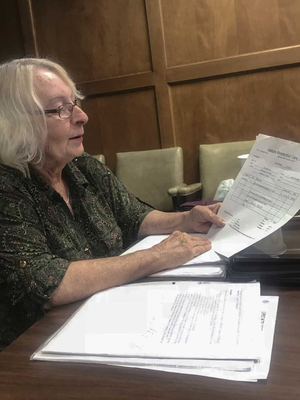 Deborah Ross, the wife of Charles Larry Ross, looks over her paperwork from Upstate Residential Care, an Anderson assisted living facility.