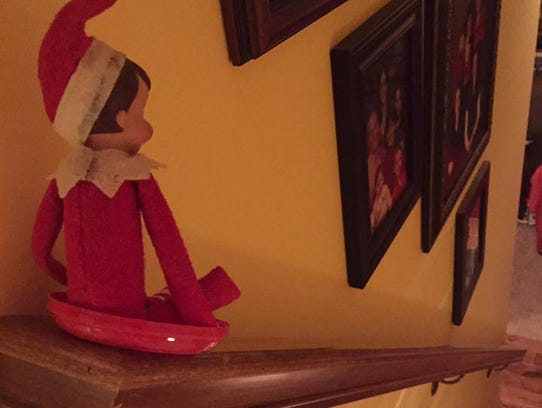 Elf on the Shelf rides down the stairs.