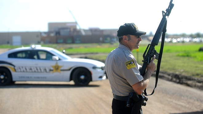 Lincoln County Sergeant Sheriff Terry Anderson guards the entrance of Harrisburg High School after a shooting in Harrisburg, SD; Wednesday, Sept. 30, 2015.