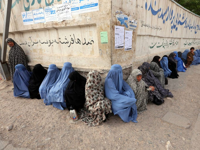 Afghan women line up to vote at a polling station in Herat, Afghanistan. Voters were choosing between former foreign minister Abdullah Abdullah and former finance minister Ashraf Ghani in a runiff election that represents the first transfer of power since U.S.-led NATO troops invaded the country shortly after the 9/11 terrorist attacks.