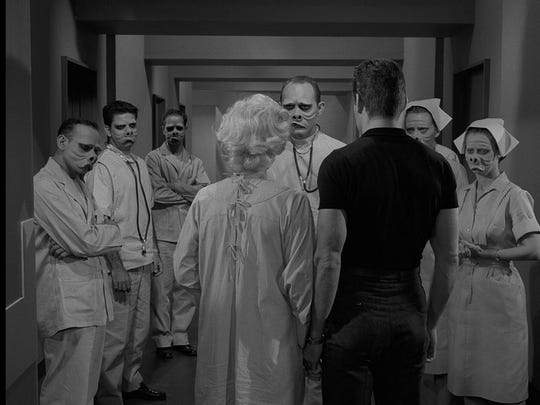 """In one of the best remembered episodes of """"The Twilight Zone"""" Donna Douglas (back to camera) wants desperately to be normal – like the folks on the hospital staff surrounding her."""