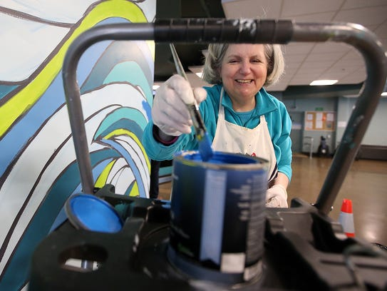 Cynthia Lait dips her brush in some fresh paint as she works on a mural inside the Bainbridge Island ferry terminal. Lait would like to see others create art in the state's ferry terminals.