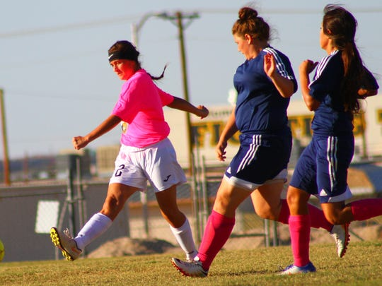 Alamogordo's Tori Borunda, left, dribbles a ball down the field past two Deming defenders Tuesday evening.