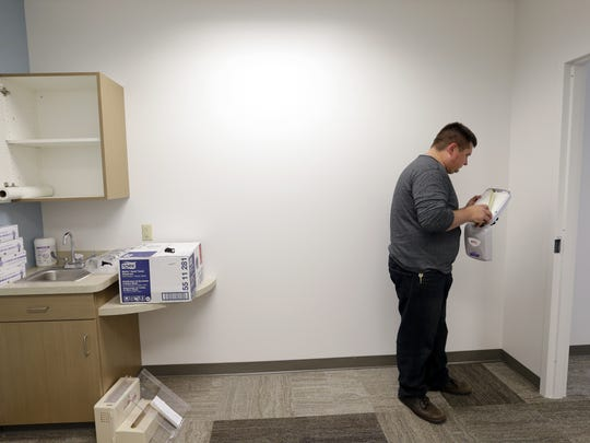 Facilities manager Matt Dorn installs medical finishes in an examining room in the new Hope Clinic & Care Center at the Appleton Alliance Church. The free clinic will open as an urgent care outlet for people in need.