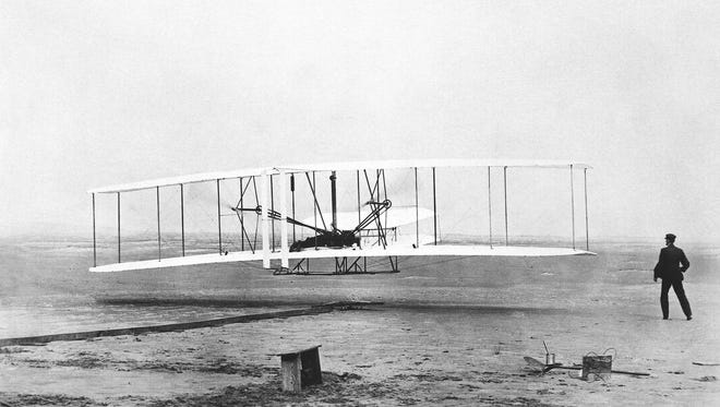 Orville at the controls, Wilbur watches. Flight is achieved. December 1903.
