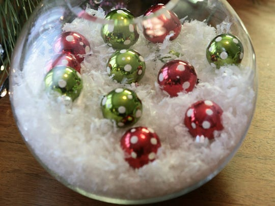 Holiday centerpieces don't have to cost a bundle. Items you might already have in the home can be repurposed to help create an elegant table.