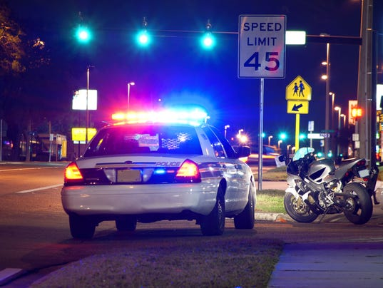 Police traffic stop at night with motorcycle pulled over