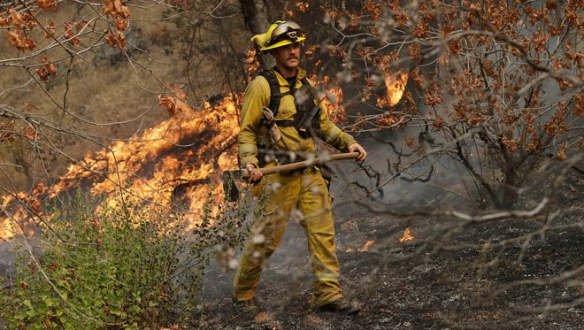 A firefighter monitors flames from an advancing wildfire  July 28, 2018, in Redding, Calif.