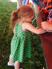 Ava Harding, 4, chooses a bookbag at Project Big Love on Saturday, July 28, 2018, at Mont Alto carnival grounds.
