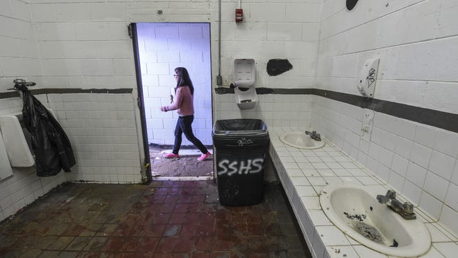 In this file photo, a girl walks past a doorless boys bathroom with clogged sinks and broken urinals at Simon Sanchez High School.