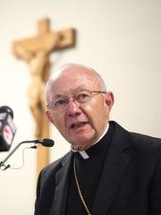 Bishop J. Douglas Deshotel addresses reporters at a