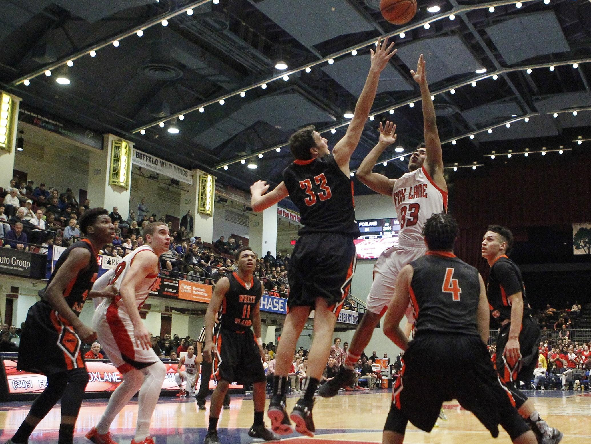 Fox Lane's Julian Francisco (33) goes up against White Plains' Spencer Lodes (33) during the boys Class AA semi-final basketball game at the County Center in White Plains on Friday, February 26, 2016.