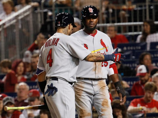 St. Louis Cardinals Dexter Fowler (25) is congratulated by teammate Yadier Molina (4) after scoring on Stephen Piscotty's single during the third inning of a baseball game against the Washington Nationals in Washington, Monday, April 10, 2017. (AP Photo/Manuel Balce Ceneta)