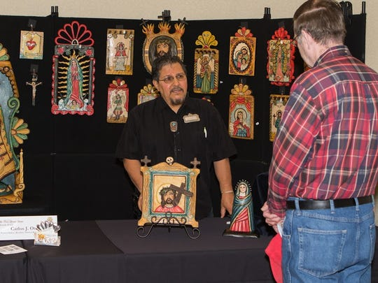 Artist Carlos J. Otero shows his handiwork to an interested art goer Saturday at the Las Cruces Spanish Market.
