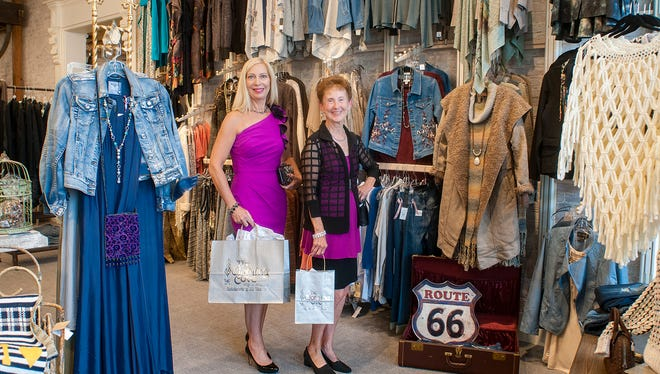 Models Karen Blazaitis of Farmington Hills (left) and Pam Wright of Farmington with some of the fashions being donated by The Clothing Cove of Milford.
