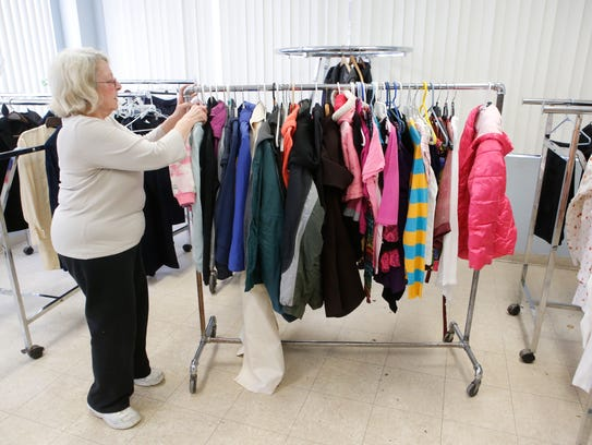 A volunteer organizes clothing donations at People