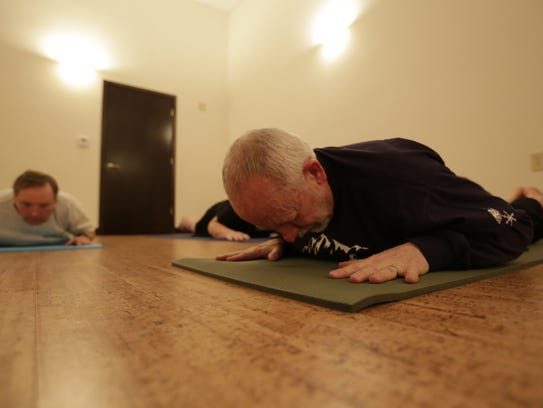 Tom Rau, 63, of Wausau, does yoga during a class March