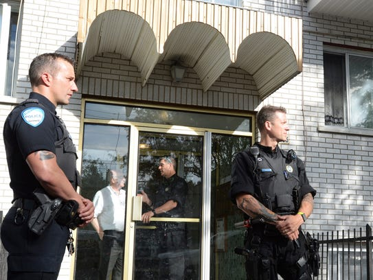 Police stand guard in front of an apartment building