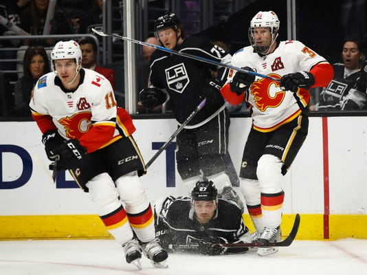 Los Angeles Kings' Alec Martinez, bottom center, falls to the ice as Calgary Flames' Mikael Backlund, left, of Sweden, and Troy Brouwer, right, chase the puck during the first period of an NHL hockey game Monday, March 26, 2018, in Los Angeles. (AP Photo/Jae C. Hong)