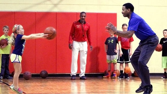 Edward McCants performs a running chest-pass drill with Emerson Williams, 8, at the McCants Reality Basketball class held at the gym at the Marion County Children Services campus in 2013. His father Brian McCants (white pants) continues to help area youth develop their basketball and life skills.