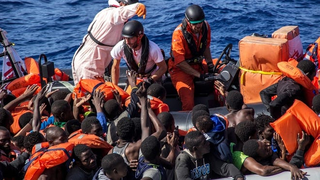 Doctors Without Borders field coordinator Michele Telaro, together with two members of the Bourbon Argos crew, distribute lifejackets during a rescue operation in the Mediterranean Sea, Oct. 26, 2016.