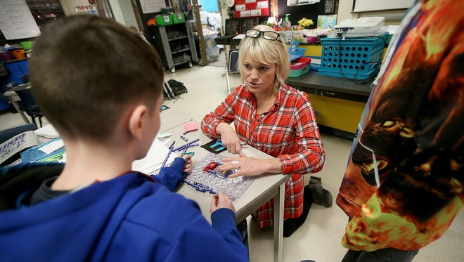 Candace Barich works with students as they use Snap Circuits as part of their electronics unit during class at John Sedgwick Middle School in Port Orchard.