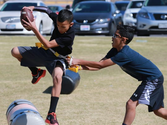 Julian Galvan, left, tries to evade having his flag pulled off by defender Nathan Espinoza during a practice session of flag football.