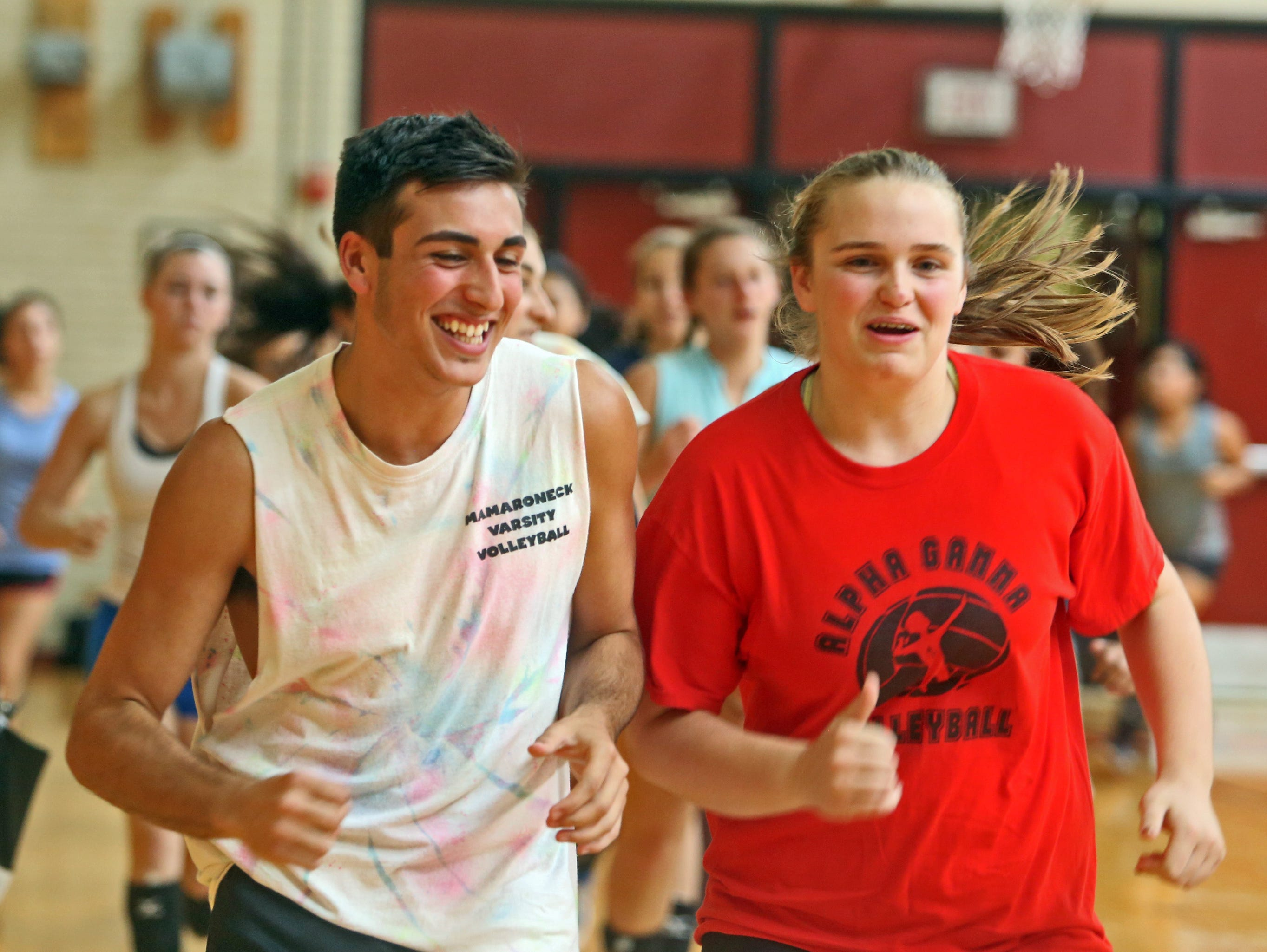 Andreo Otiniano, a senior at Mamaroneck High School, and a member of the girls volleyball team, warms up with teammate Maddie Sach at the start of practice Sept. 16, 2015. Otiniano played with the team as a sophomore, and still practices with the team and is on the roster, but present Section 1 rules do not allow him to play in matches.