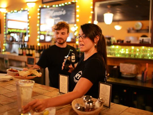 Janice Terry serves a customer at the bar at Marco's Pizzeria off Merrimon Ave. in North Asheville.