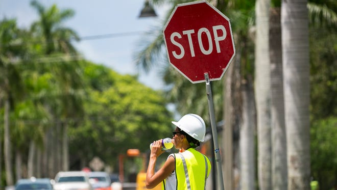 Flagger Lindsey Slawson drinks Gatorade to try to stay hydrated while working in the heat on McGregor Boulevard on Wednesday.