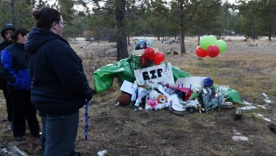 People gather at a memorial near the site where the body of Dejon Smith was found behind a house on Rancho Circle in South Lake Tahoe on Dec. 16, 2014.