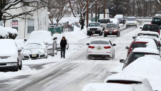 Drivers and a pedestrian navigate Hooker Street in Jamesburg, Tuesday, Feb. 17, 2015, after several inches of snow blanketed Middlesex County.