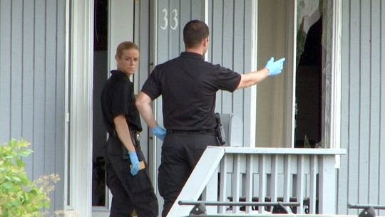 Investigators are shown on the front porch of a Miiddletown Township home, next to a smashed window, at 33 Bayview Parkway in the East Keansburg section of the township where a man holding his 17-month-old son hostage was shot and killed by police early Wednesday.